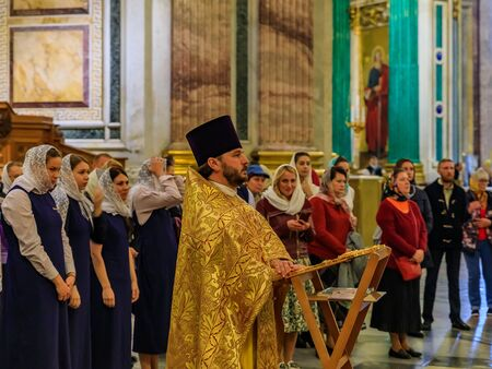 Saint Petersburg, Russia - September 10, 2017: Russian Orthodox priest in traditional clerical clothing serving mass and parishioners behind him in the Saint Isaacs Russian Orthodox Cathedral