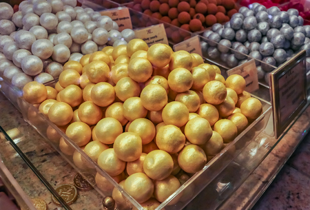 Saint Petersburg, Russia - October 05, 2015: Fancy gold and silver covered chocolate candy made in house on display at the famous grocery store Eliseevsky on Nevsky Prospect