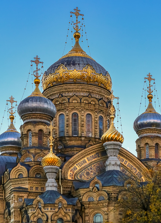 Ornate golden domes and crosses of the Russian Orthodox Church of the Assumption of Mary on the river Neva in Saint Petersburg Russia