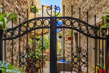 Wrought iron gate in the narrow streets of the medieval Old town with shops, cafes and restaurants in Budva, Montenegro in the Balkans
