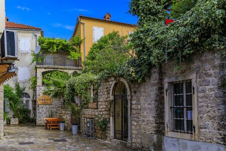 Budva, Montenegro - May 30, 2019: Picturesque narrow streets of the well preserved medieval Old town with shops, cafes and restaurants in the Balkans