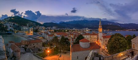 Sunset aerial view of Budva Old Town from the Citadel with the Holy Trinity church and Adriatic Sea in the background in Montenegro, Balkans