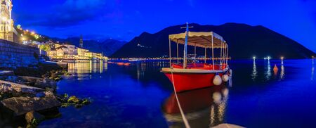 Long exposure sunset panoramic view of Kotor Bay and a docked boat in the postcard perfect town of Perast, Montenegro with mountains in the background