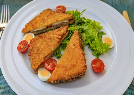 Gebratenes Sandwich, Krapfen, mit Ziegenkäse und Njeguski Prsut, serviert mit Tomaten, gekochtem Wachtelei und Salat, traditionelles montenegrinisches Essen
