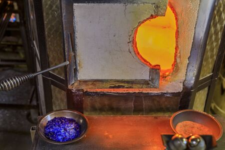 Glass blowing furnace and table with with crushed glass and tools at a glass makers workshop set up for the traditional glass blowing process Imagens