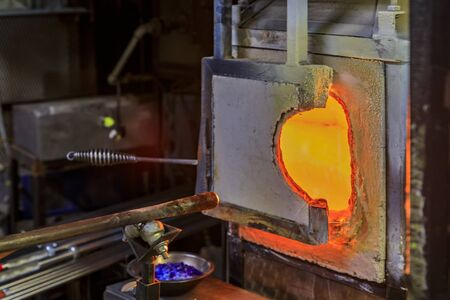 Glass blowing furnace and table with various glass blowing tools at a glass makers workshop set up for the traditional glass blowing process