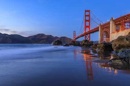 Famous Golden Gate Bridge view from the hidden and secluded rocky Marshalls Beach at sunset in San Francisco, California