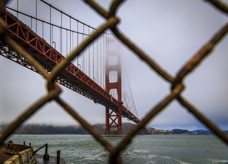 The famous Golden Gate bridge viewed through a rusty chain link fence on a cloudy summer day with low hanging fog rolling in San Francisco, California