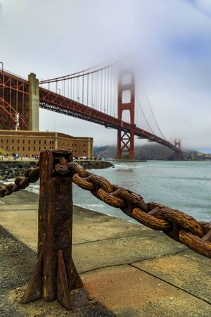 The famous Golden Gate bridge on a cloudy summer day with low hanging fog rolling in San Francisco, California