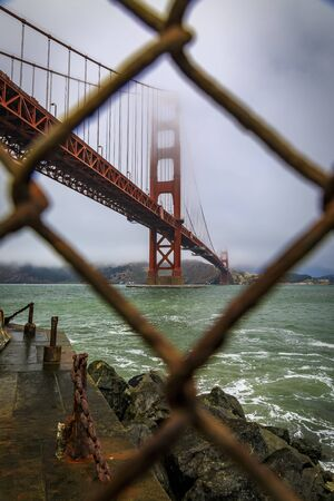 The famous Golden Gate bridge viewed through a rusty chain link fence on a cloudy summer day with low hanging fog rolling in San Francisco, California Banco de Imagens - 132112045