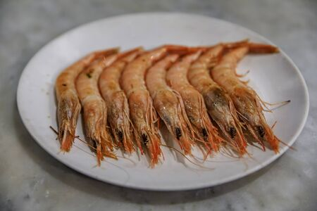 Traditional gambas a la plancha or grilled shrimp with garlic tapas prepared on a hot iron plate at a restaurant in Madrid, Spain