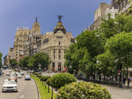 Madrid, Spain - June 4, 2017: View of Metropolis, one of the most beautiful buildings and Calle de Alcala with street traffic and dramatic blue sky Editorial