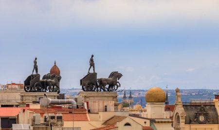 Madrid, Spain - June 4, 2017: City rooftops and neoclassical quadriga Roman Chariot statues on Banco Bilbao Vizcaya BBVA bank building built in 1923