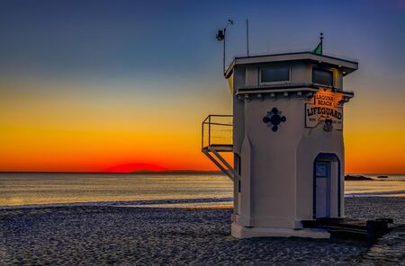 Incredible colors of sunset in Laguna Beach, famous tourist destination in California, USA with a lifeguard station in the foreground 免版税图像