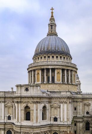 View of the dome of the famous St. Pauls Cathedral in city center on a cloudy day in London, United Kingdom
