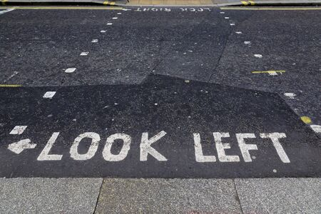 Look left sign written on the pavement at the pedestrian or puffin crossing in central London, England Imagens