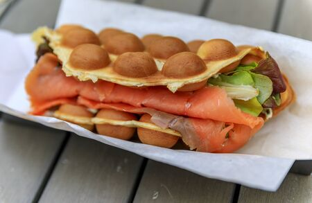 Close up of a ready to eat bubblewrap or bubble waffle smoked salmon sandwich from a fast food restaurant in London, UK Imagens