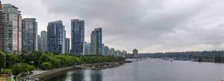 Coal Harbor with downtown buildings, boats and reflections in the water in Vancouver, Canada