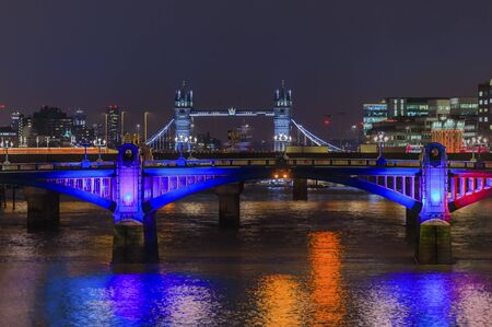 City skyline after sunset with the famous Southwark Bridge and Tower Bridge across Thames river with night lights on in London, United Kingdom