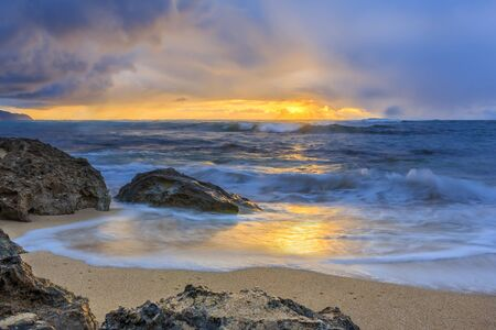 Waves rolling onto a rocky beach with a stunning sunset and rain in the background in North Shore, Oahu, Hawaii, long exposure Imagens