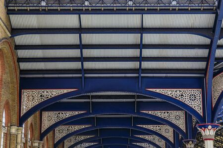 Intricate wrought iron decorative roof trusses details at the Liverpool Train Station in London, United Kingdom