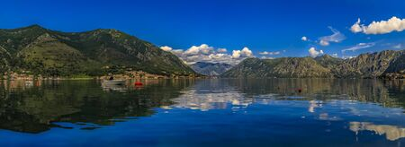 Panoramic view of Kotor Bay or Boka Kotorska with mountains reflecting in crystal clear water in the Balkans, Montenegro on the Adriatic Sea