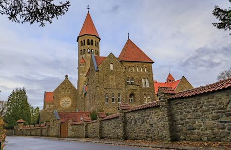19th century neo romanesque Clervaux Abbey, monastery of Saint-Maurice and Saint-Maur Benedictines in Luxembourg surrounded by a forest in the fall