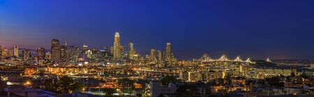 San Francisco skyline panorama after sunset with city lights, the Bay Bridge and highway trail lights leading into the city