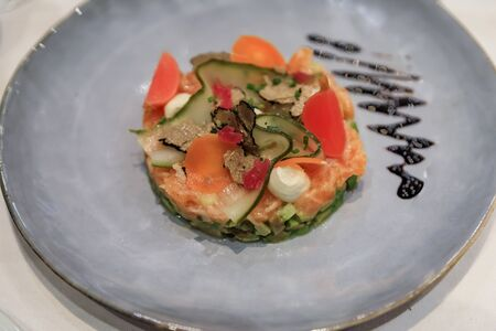 Salmon carpaccio appetizer with slices of a black truffle on a plate at a luxury restaurant in Nice, France