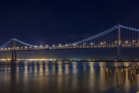 San Francisco Bay Bridge on a clear night, lit up by yellow and blue lights, reflecting of the water in the Bay, long exposure 免版税图像