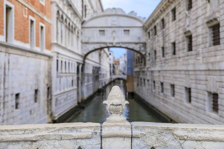 Carved pine cone on Ponte della Paglia balustrade with a view of Bridge of Sighs on Rio del Palazzo and the Doges, Palace in Venice Italy at sunrise