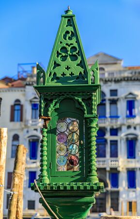 Ornate antique green lamp with wodden and glass detial at a gondola stop with traditional Venetian Gothic buildings in the background in Venice Italy Stock fotó