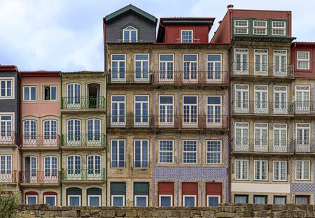 Facades of traditional houses decorated with ornate Portuguese azulejo tiles in the famous Ribeira neighborhood in Porto, Portugal