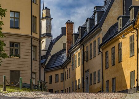 Traditional old houses and cobblestone road in the heart of Stockholm city center, the old town part of Sodermalm, Sweden Stock Photo