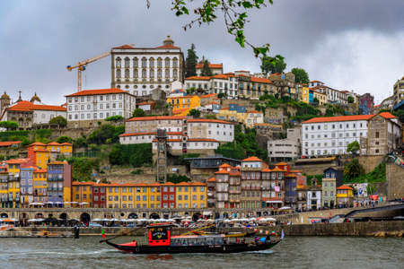 Porto, Portugal - May 31, 2018: Facades of traditional houses with azulejo tile in Ribeira and tourist rabelo boat on Douro in Porto Portugal 新聞圖片