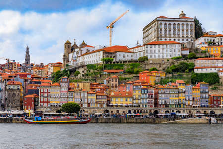 Porto, Portugal - May 30, 2018: View across the Douro onto the facades of traditional houses with azulejo tile in Ribeira and tourist rabelo boats Editoriali