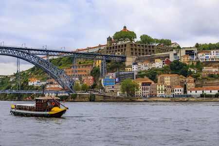 View across the Douro river and Dom Luis I bridge in Vila Nova de Gaia and tourist boats that were used for transporting port wine in Porto, Portugal