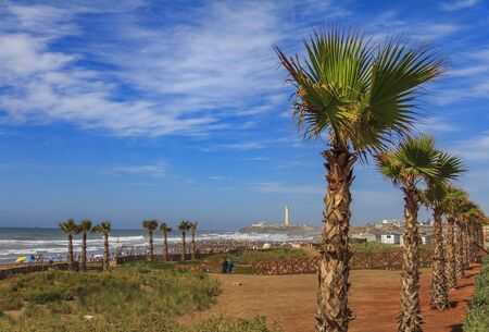 Palm trees along the Atlantic Ocean shore and unidentifiable people walking on the beach with the lighthouse in the background in Casablanca, Morocco