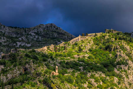 Church of Our Lady of Remedy, Roman Catholic church on Saint John Mountain along Old Town ancient city walls against stormy skies, Kotor, Montenegro 写真素材