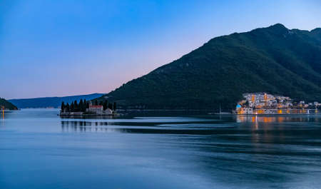 Panoramic view of Saint George island with a centuries-old monastery and tall cypress trees in the famous Kotor Bay near Perast, Montenegro at sunset