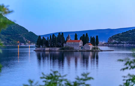 Scenic view of Saint George island with a centuries-old monastery and tall cypress trees in the famous Kotor Bay near Perast, Montenegro at sunset 写真素材