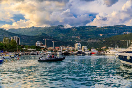 Budva, Montenegro - June 1, 2019: Anchored boats in the port and marina by the medieval Old town on the Adriatic Sea at sunset