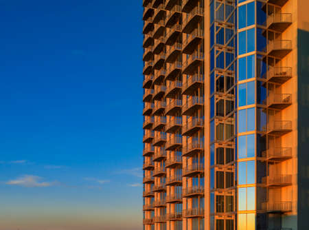 View onto modern new construction skyscraper building in downtown Austin, Texas at golden hour of sunset, the sky reflecting in the windows glass