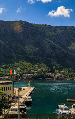 Kotor, Montenegro - May 30, 2019: Emerald green waters of Kotor Bay or Boka Kotorska, mountains and boats docked by the pier in the port 報道画像