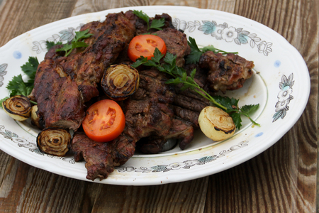 Grilled pork meat with onion, tomato and parsley on wooden table