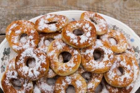 Sweet, flavorful donuts in powder in a plate on a wooden table