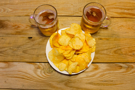 Chips on a plate to beer on a wooden table