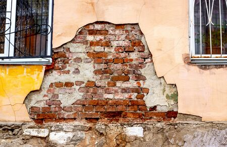 A worn-out building facade with crumbling stucco shows the texture of the red brickwork of the house. Closeup of part of the wall of an old house with barred windows