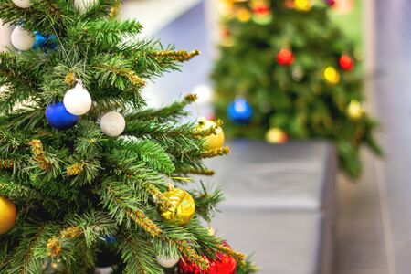 Decorated Christmas tree with with the background of the second Christmas tree. Bright Christmas wallpaper with two New Year's conifers, one out of focus. Place for an inscription, congratulations Stockfoto - 134866934