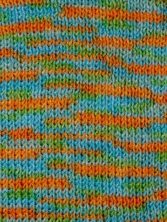 Knitted woolen colored background. Texture of multi-colored wool close-up. Knitted fabric, handmade, knitting. Yellow, green and blue scarf pattern. 版權商用圖片